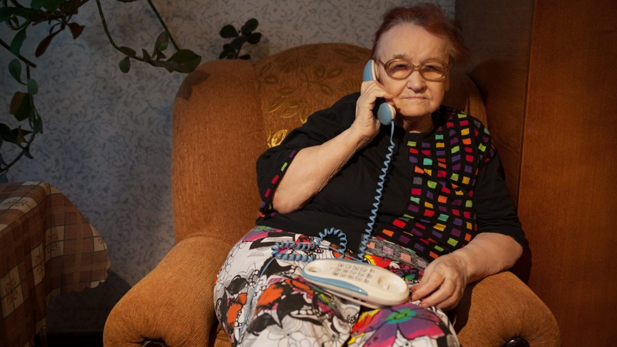 Old woman talking on the home phone sitting in the arm-chair in the evening