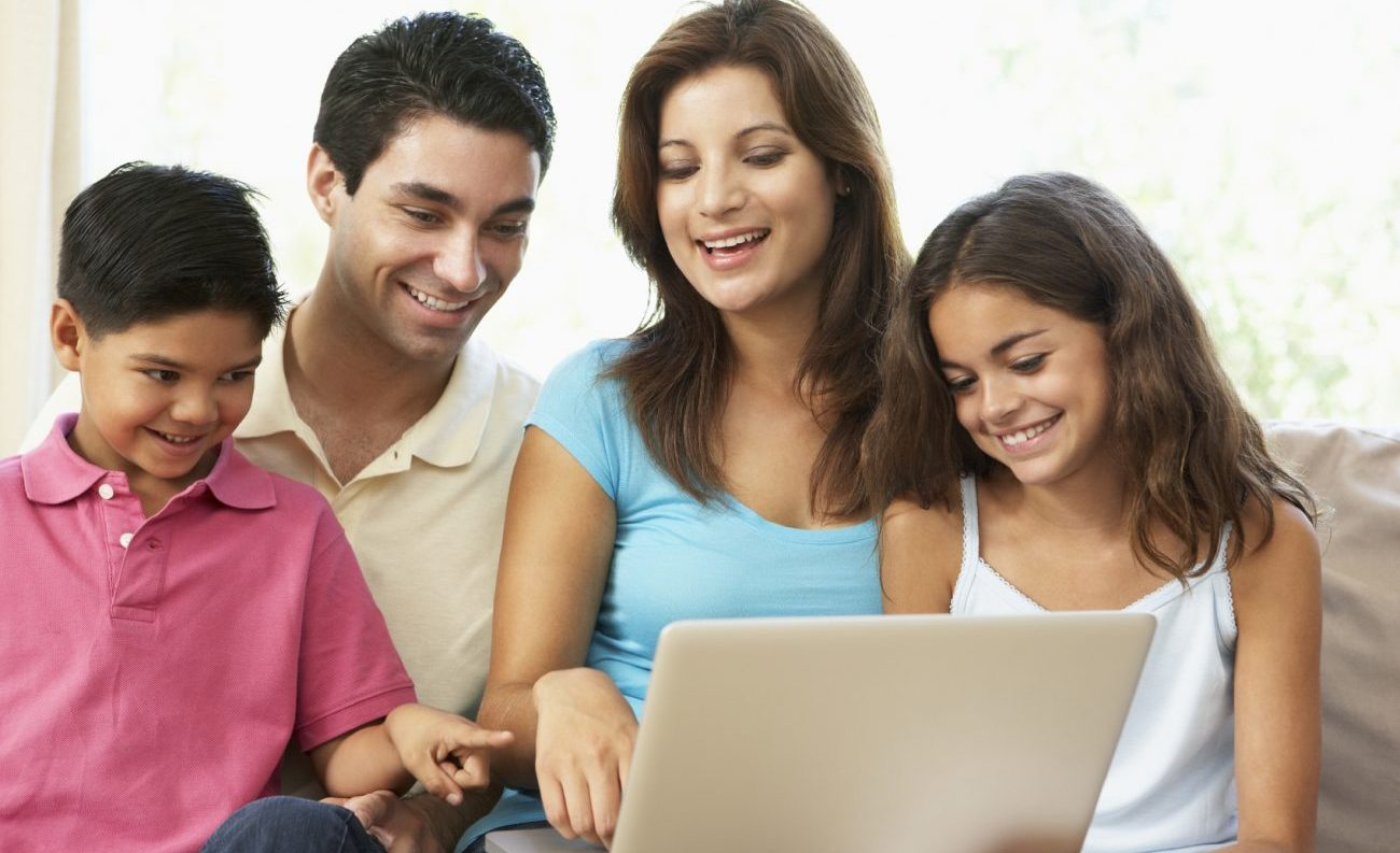 Family Sitting On Sofa At Home With Laptop