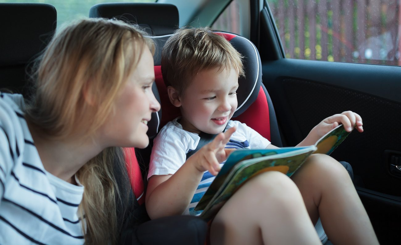 Mother and little son in the car. Woman watching boy looking through the book. Kid sitting in child safety seat
