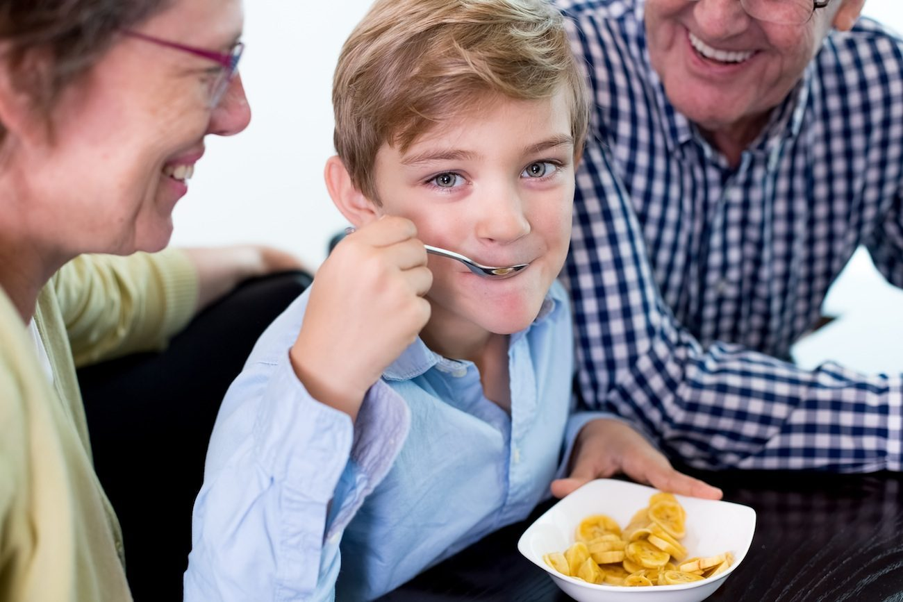 Closeup of smiling at camera little boy eating sliced banana and sitting at table with his grandparents