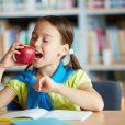 Portrait of healthy schoolgirl eating big red apple